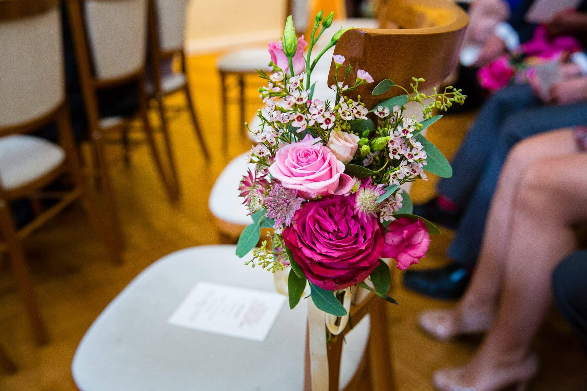 Pink flowers tied to chair back - Farnham Castle Wedding Chairs