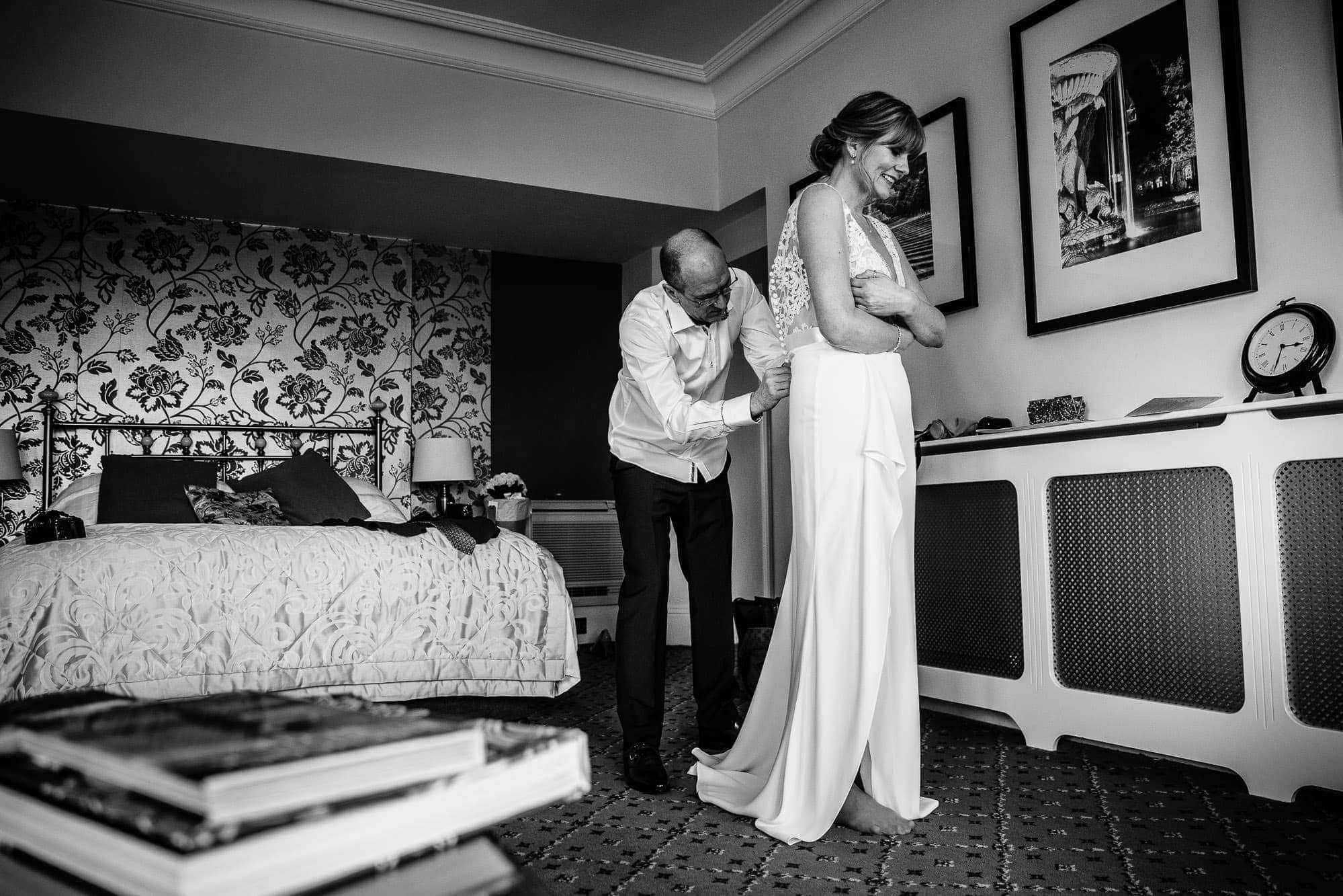 Groom doing up wedding dress