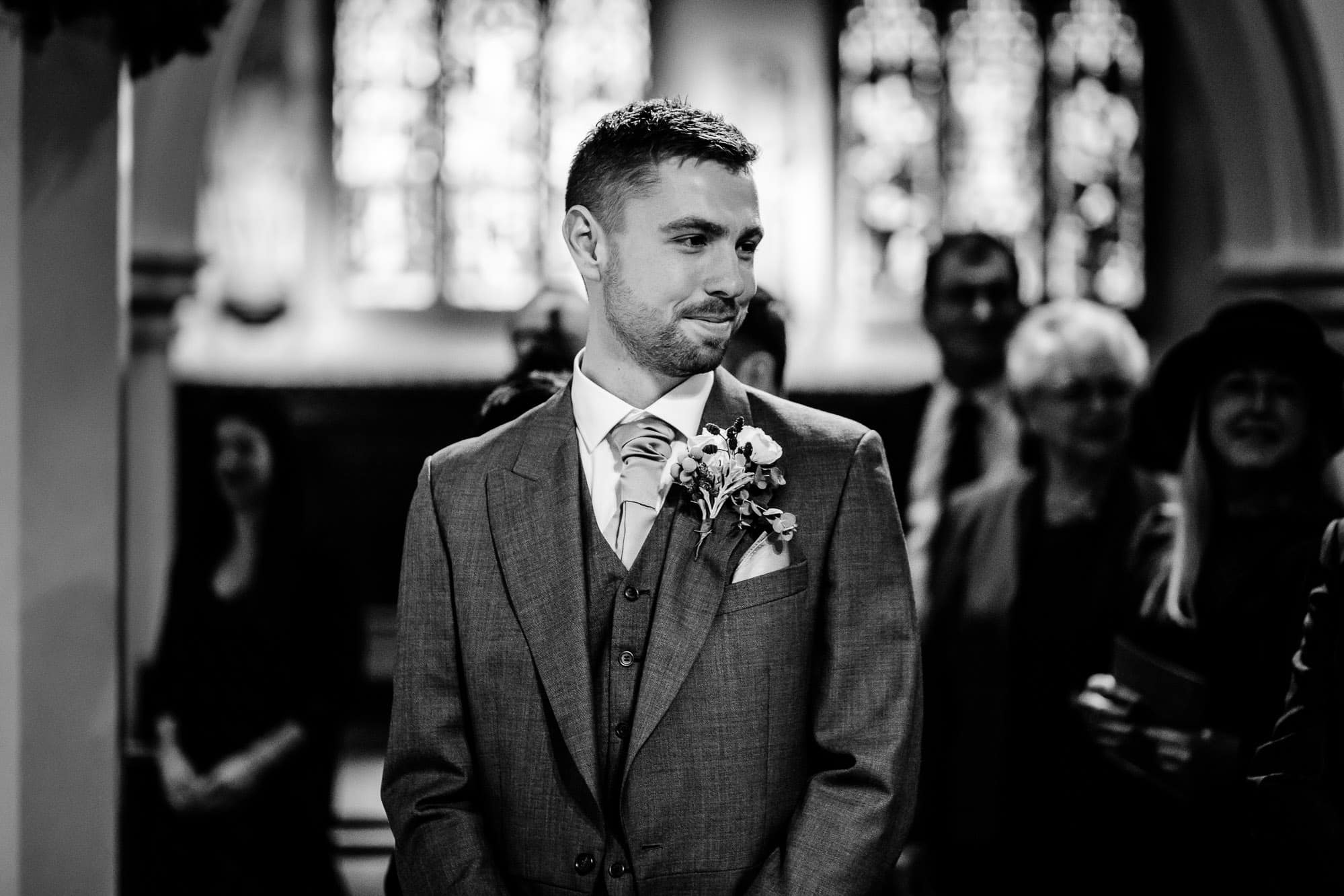 Groom watching bride walk down aisle St James Parish Church, Weybridge