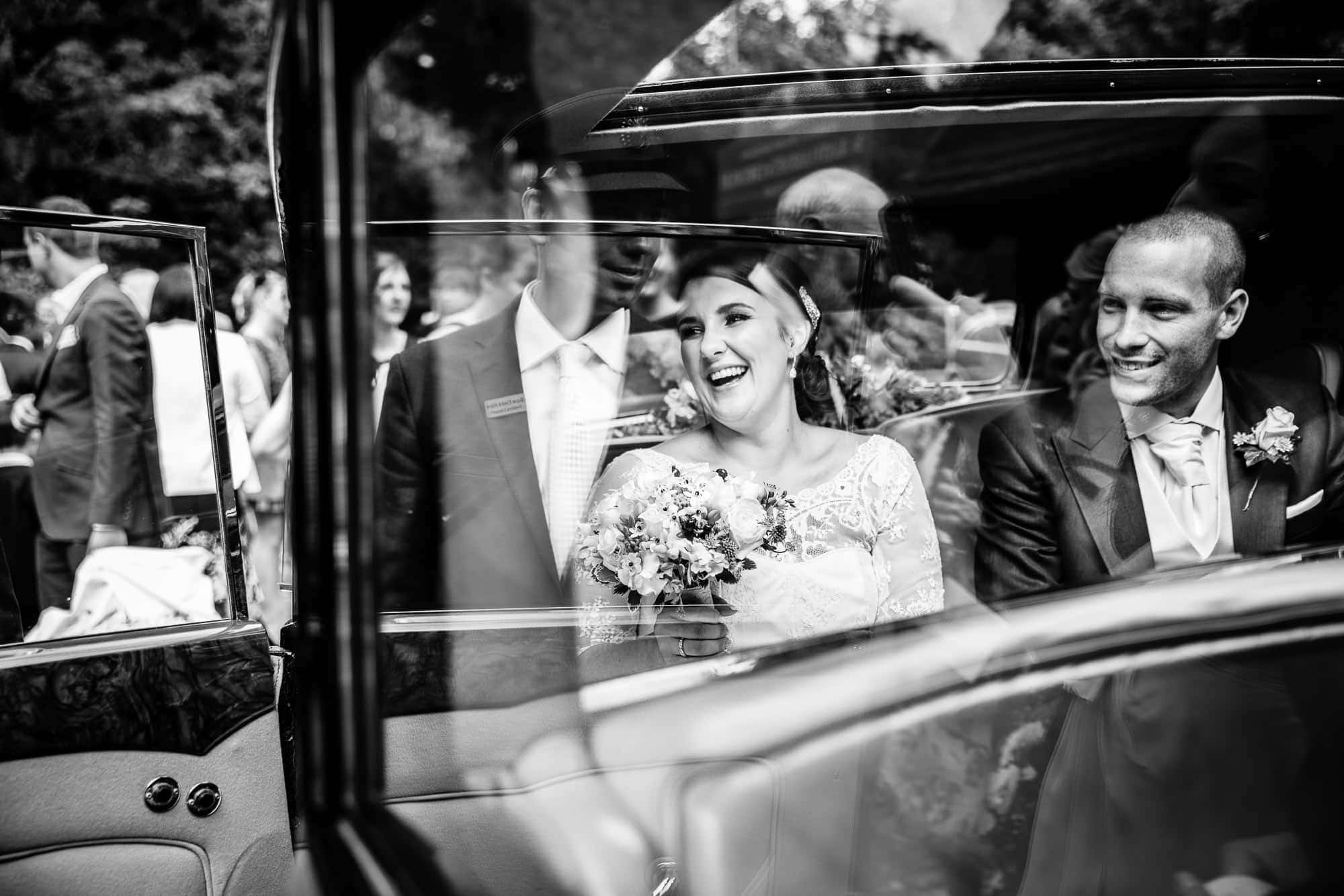 Surrey Wedding Photographer - Bride and Groom in wedding car - Reflections