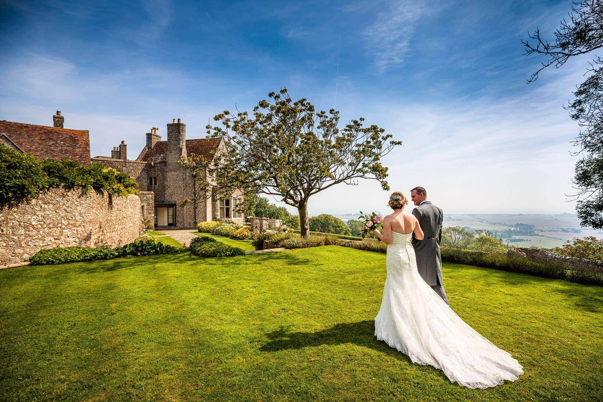 Couple walking away across grass from wedding ceremony at Lympne Castle in Kent. Blue sky, summers day.