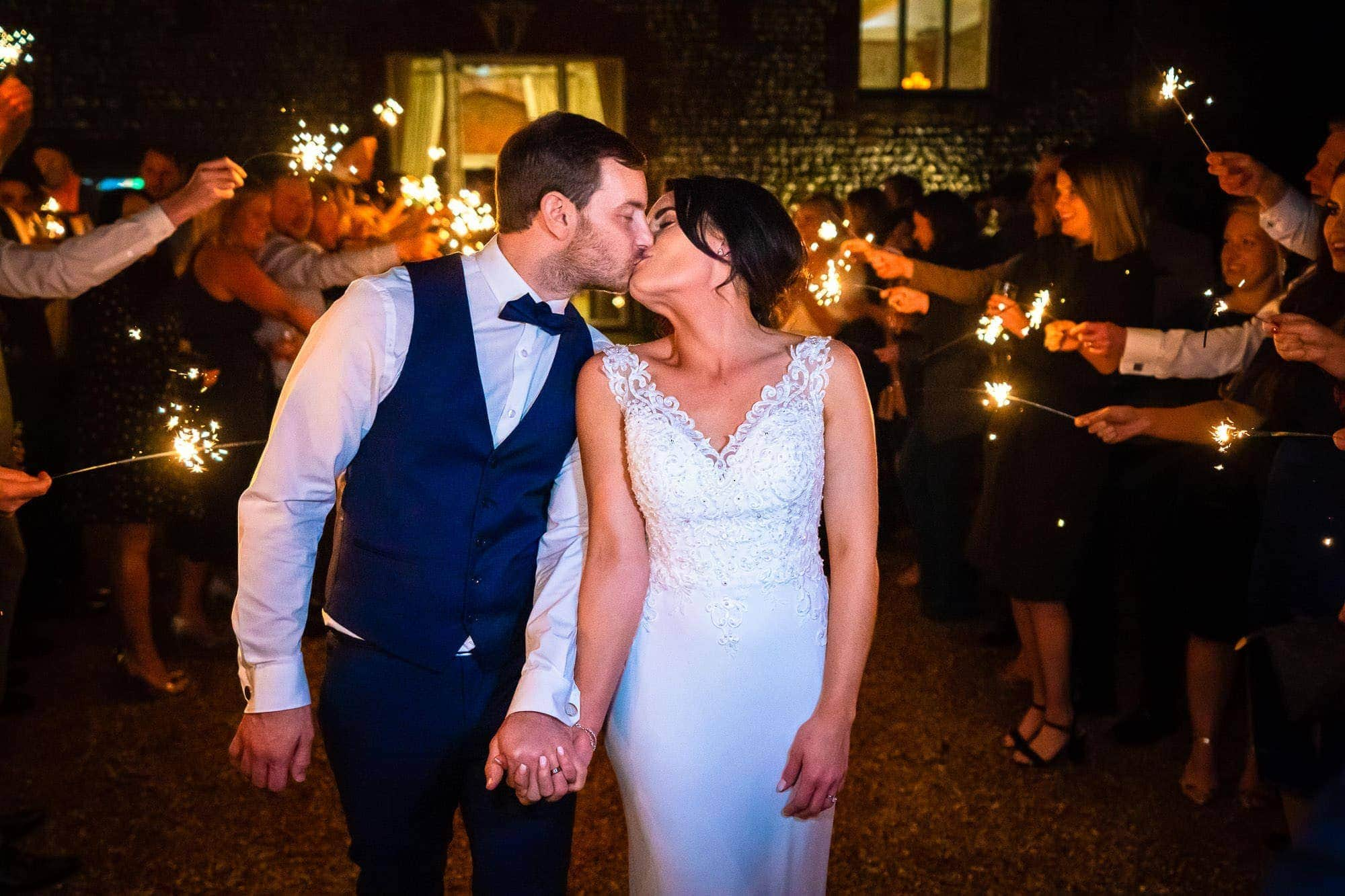 Couple Kissing with Guests holding Sparklers - Farbridge Wedding