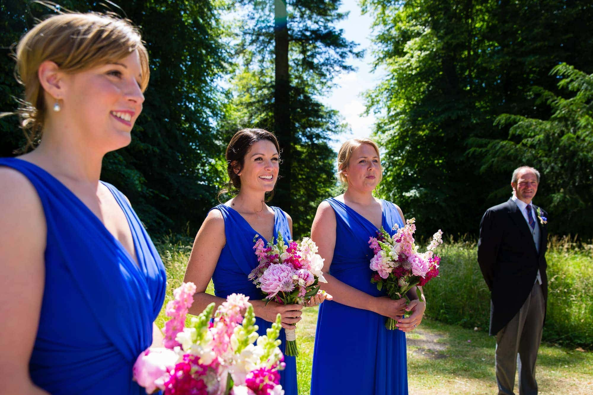 Bridesmaids in chelsea blue dresses holding bouquets of country garden flowers