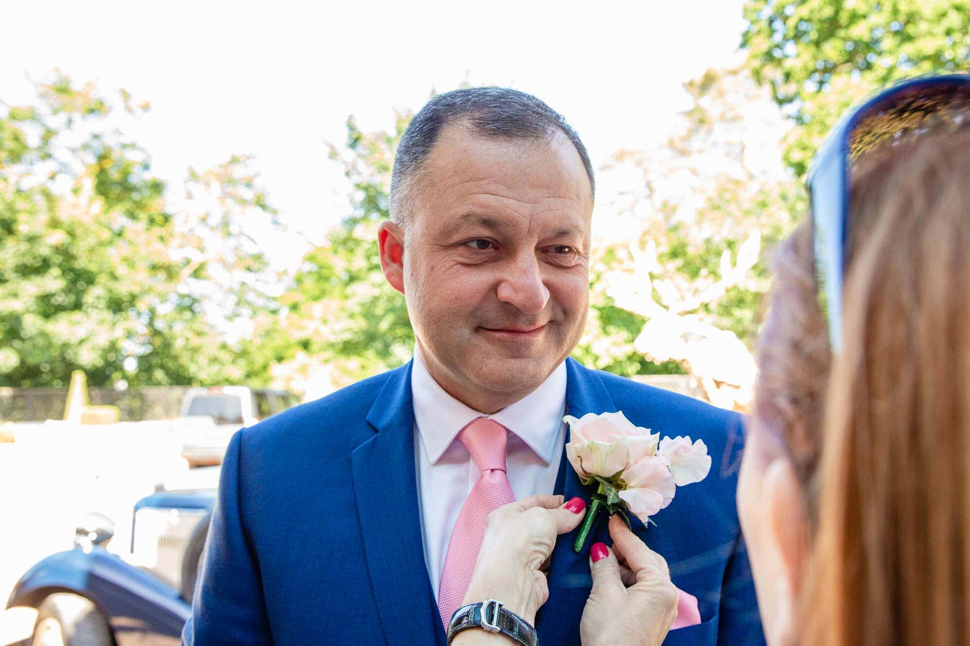Groom in blue suit having pink flower button hole put on