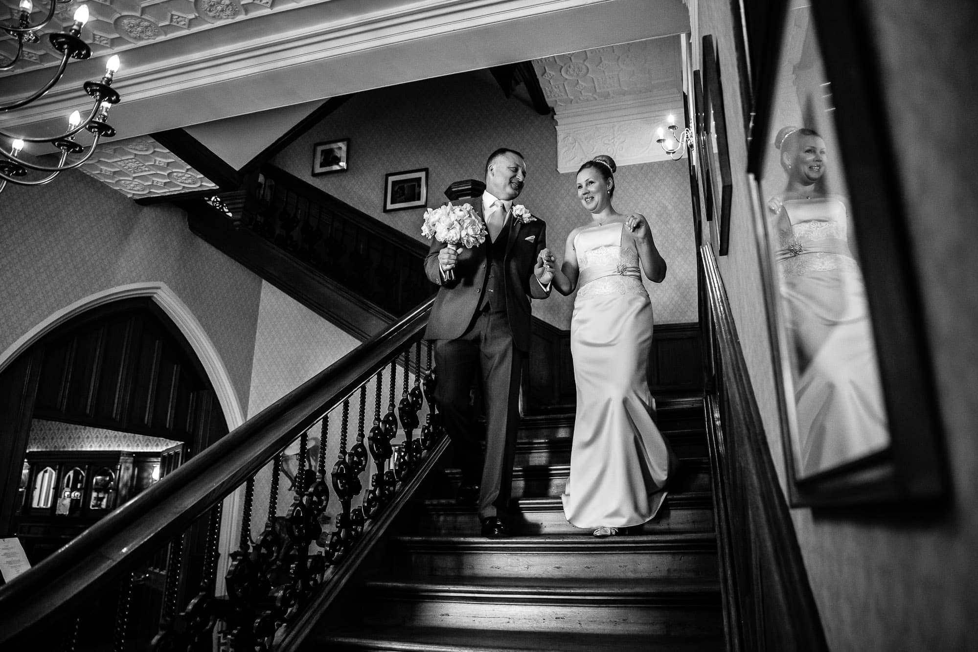 Bride & Groom walking down stairs at Oakley Court Wedding