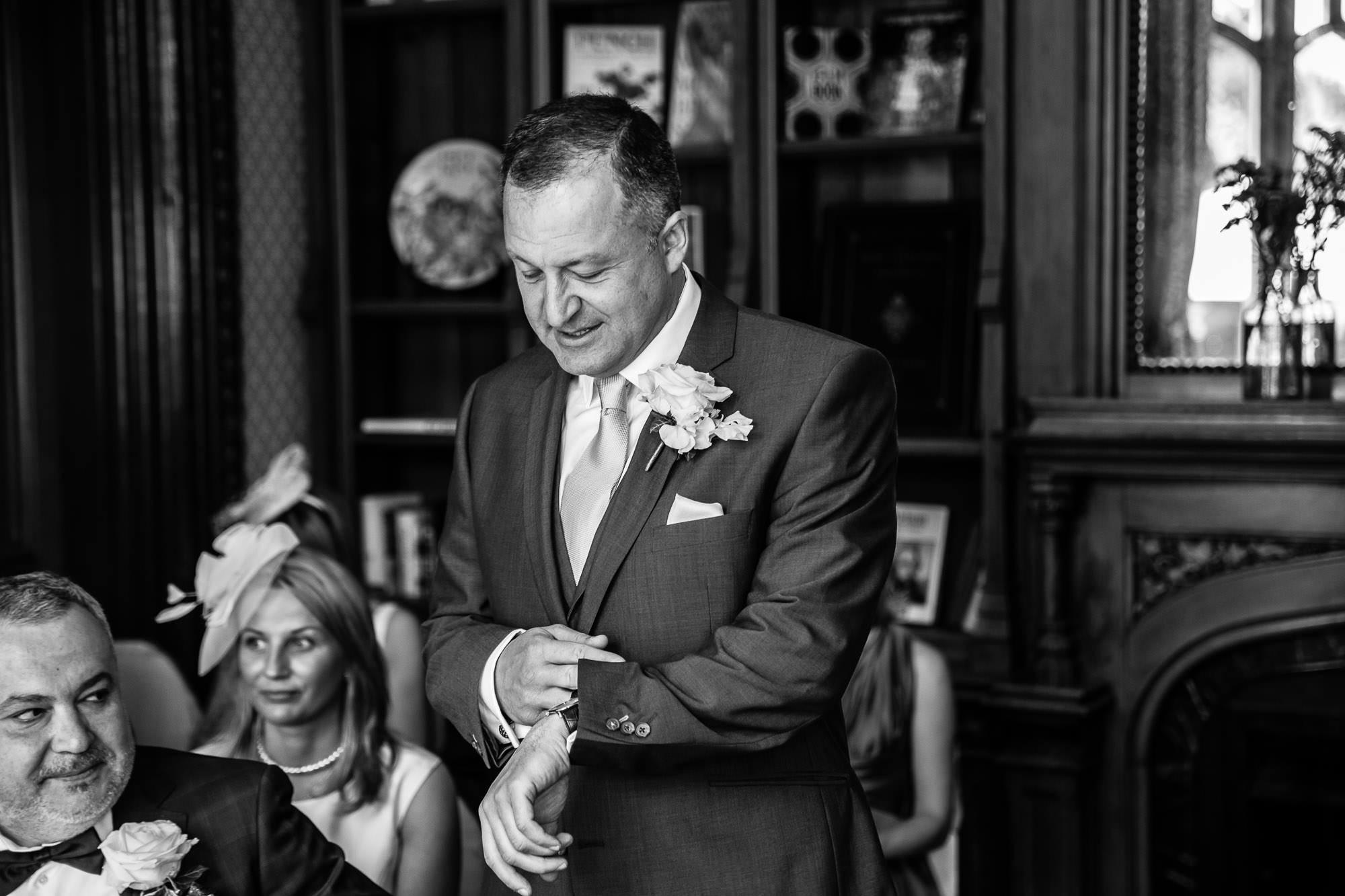 Groom checking watch Oakley Court Wedding