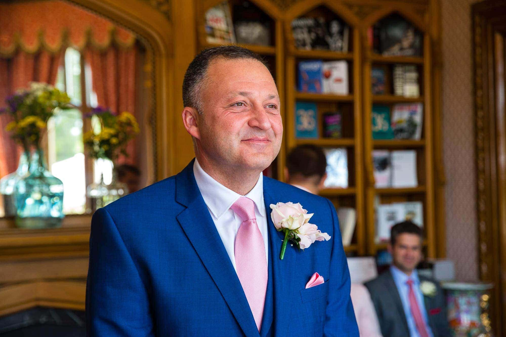 Groom in light blue suit, pink tie, pink buttonhole