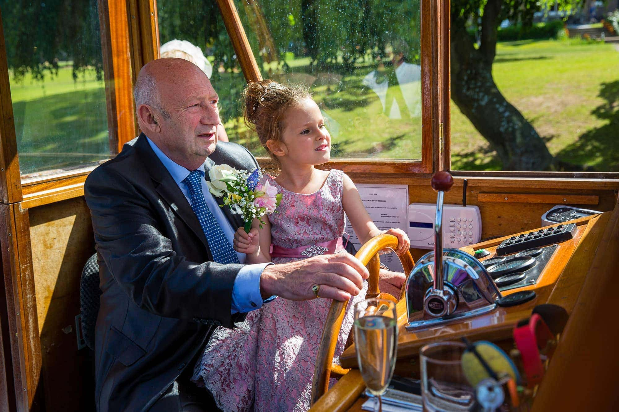 Grandfather and Granddaughter driving boat on Thames