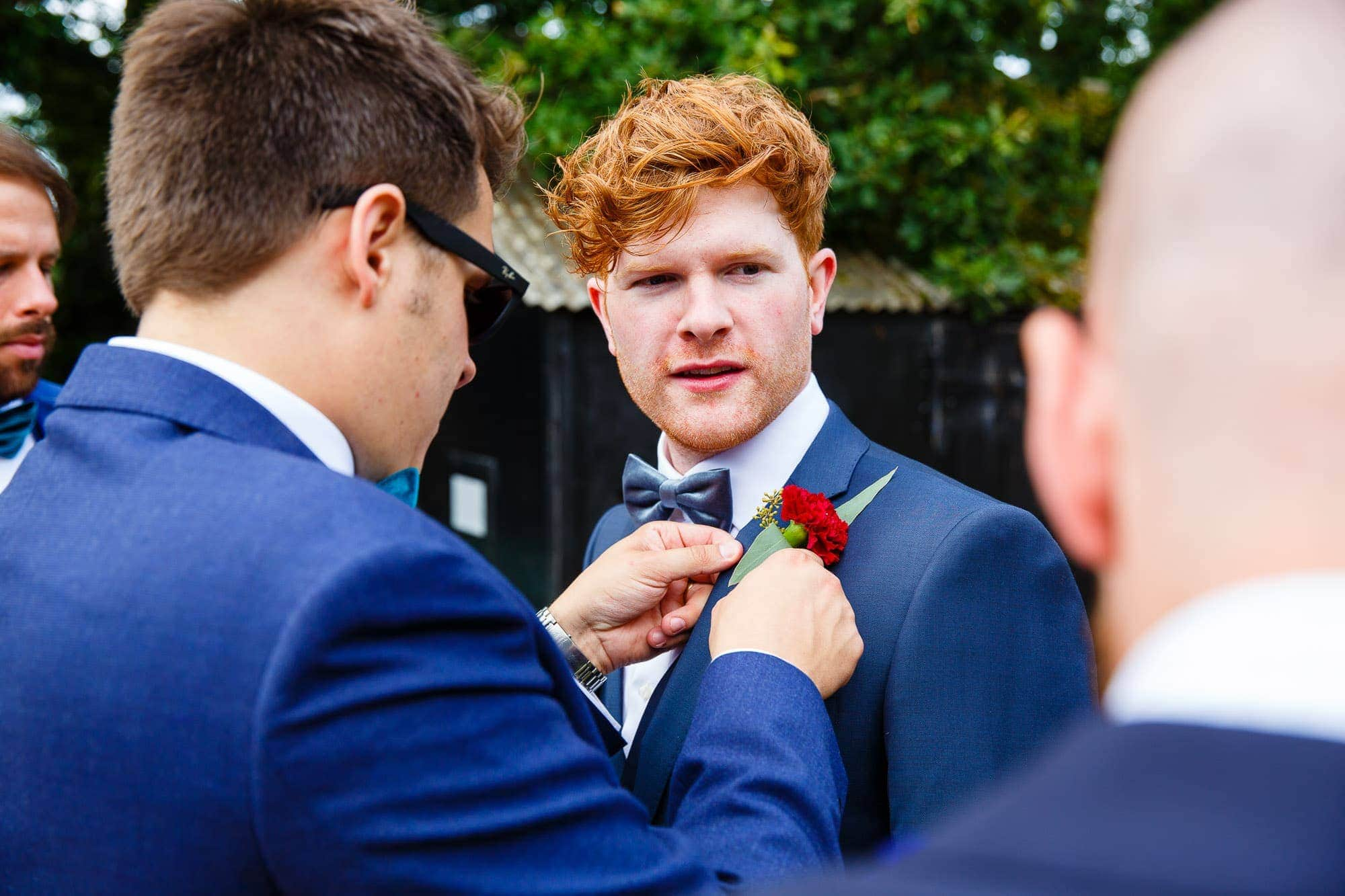 Groom having button hold pinned on