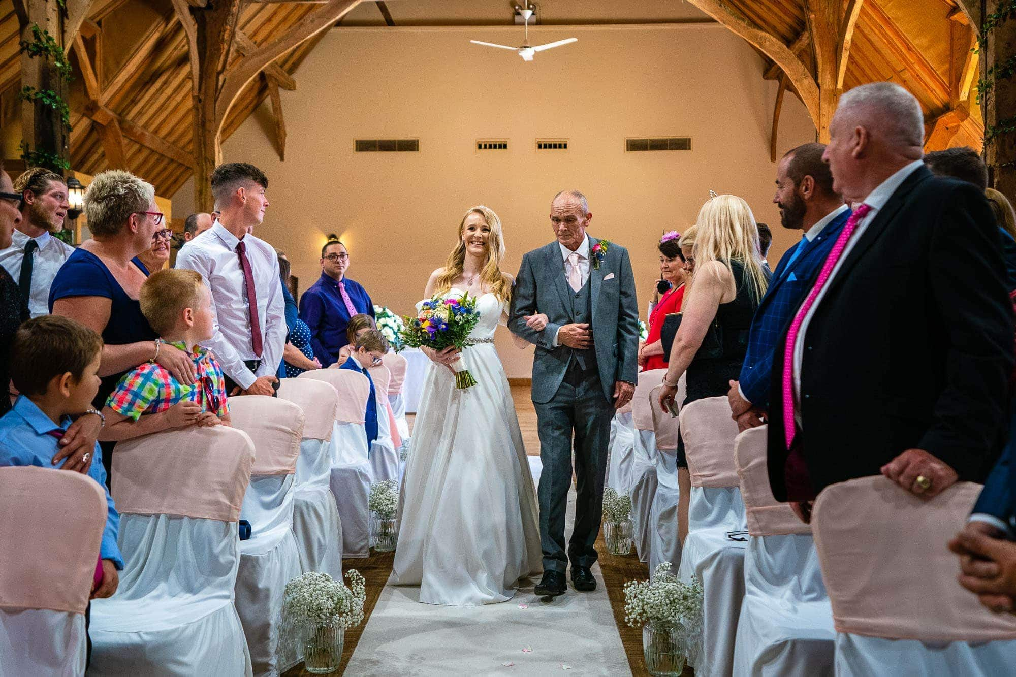 Norton Park Hotel Wedding Photographer - Bride walking down the aisle with her father in the wedding barn