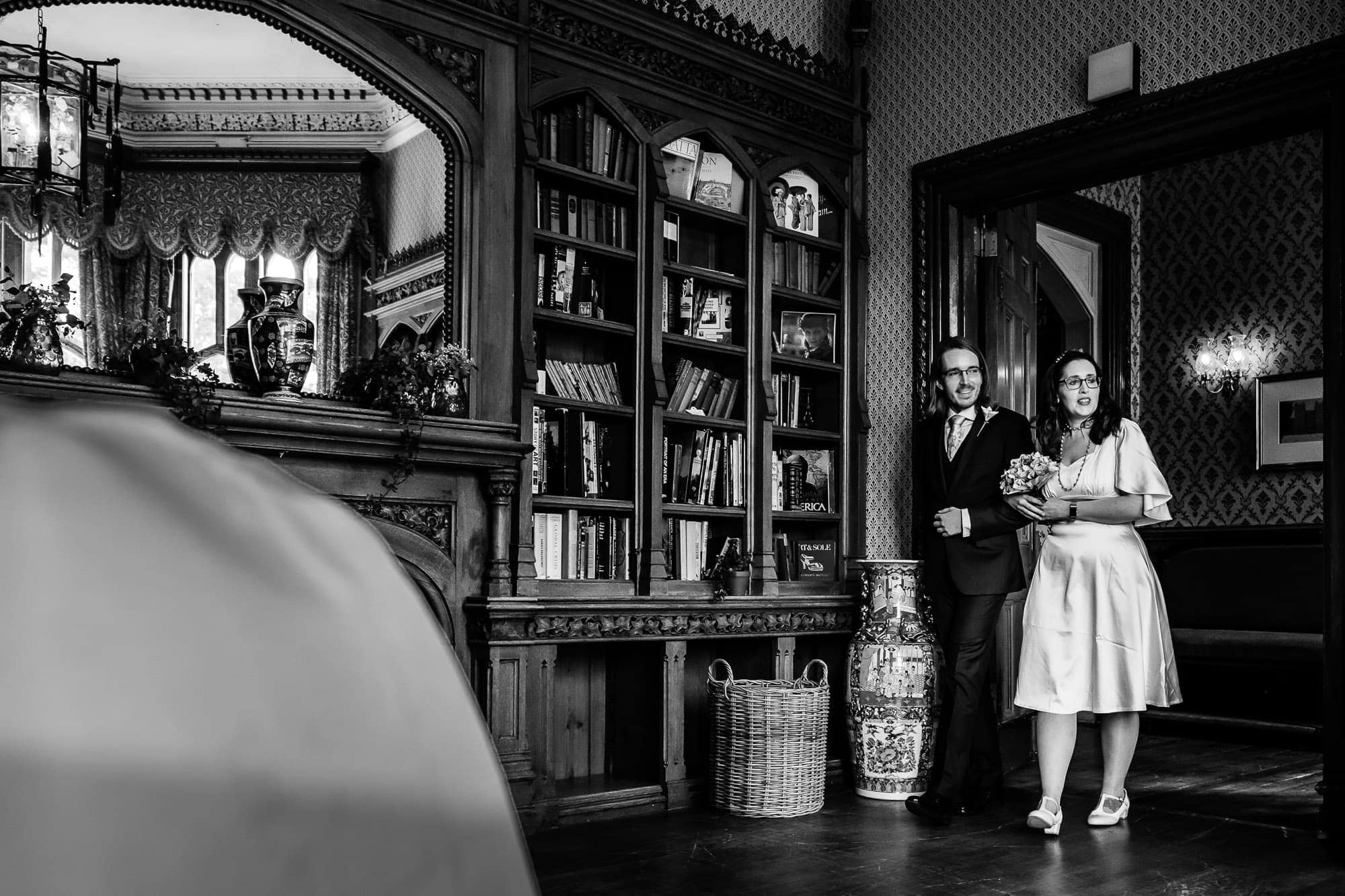 Couple walk into wedding ceremony arm in arm. B&W photo.