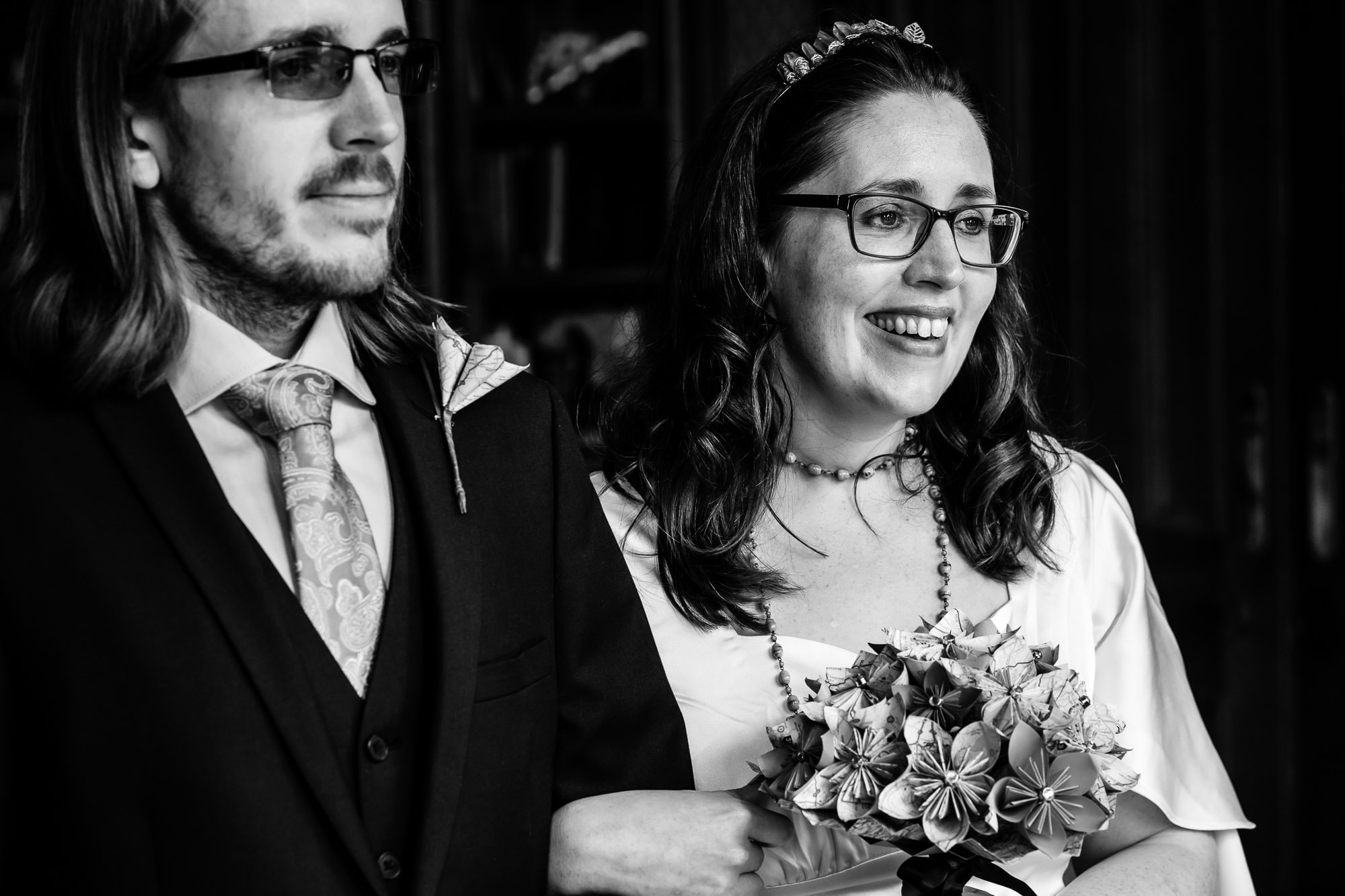 Bride and groom, during elopement wedding, bride is laughing. B&W photo.
