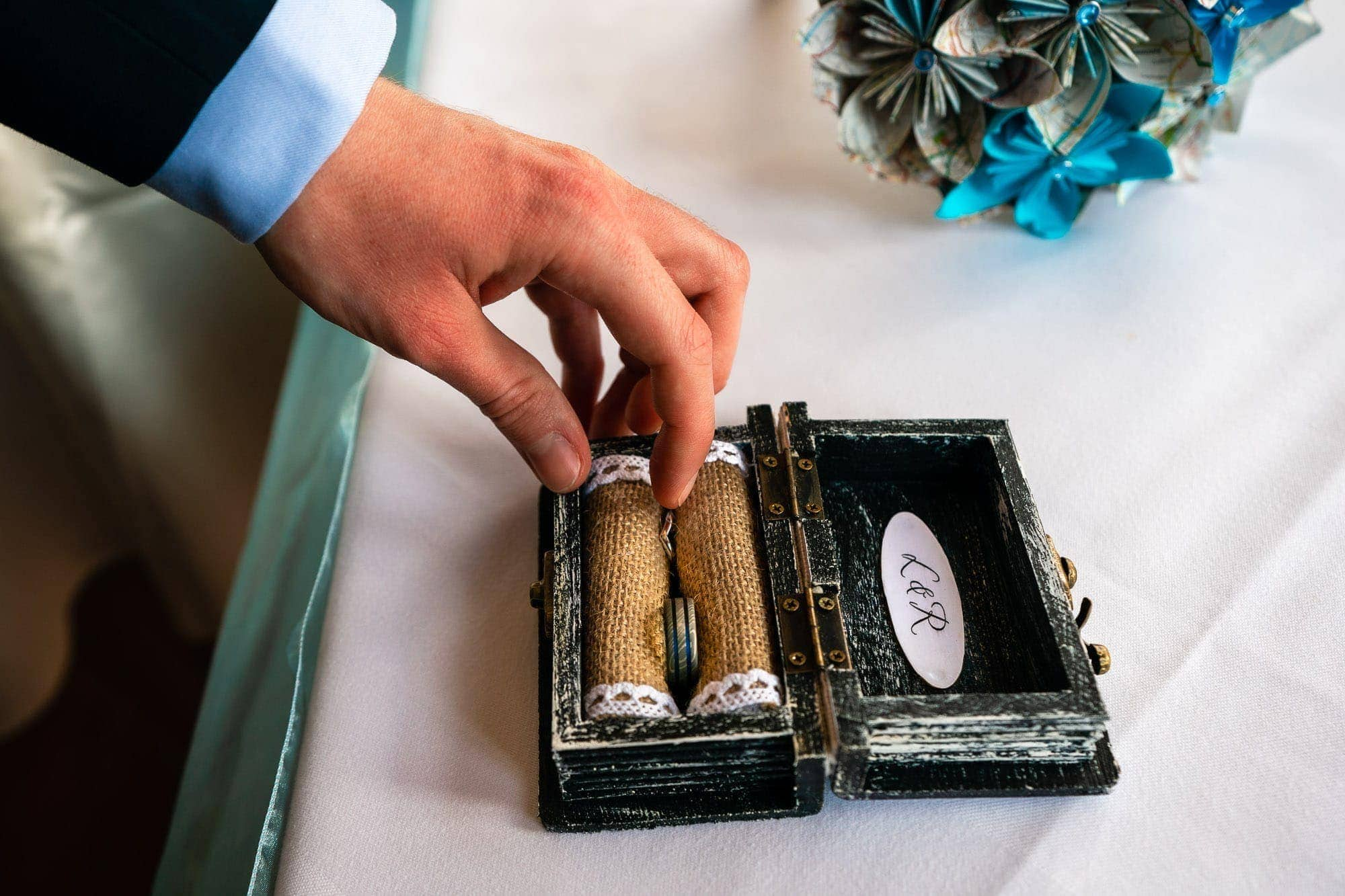 Groom taking ring out of ring box during their wedding ceremony.