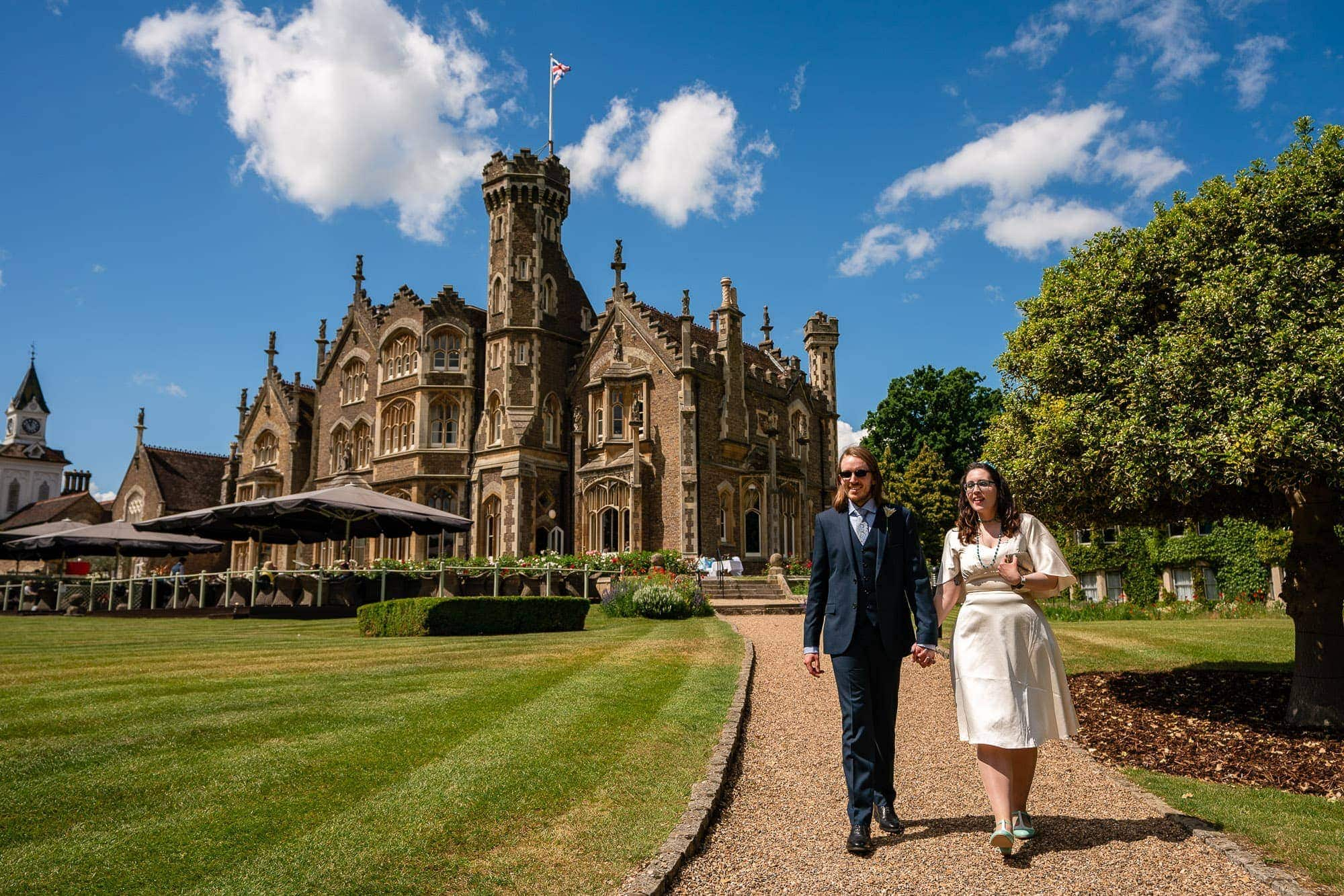 Bride & Groom, walking hand in hand in the gardens of Oakley Court, in Windsor. Hotel in background, blue sky white clouds.