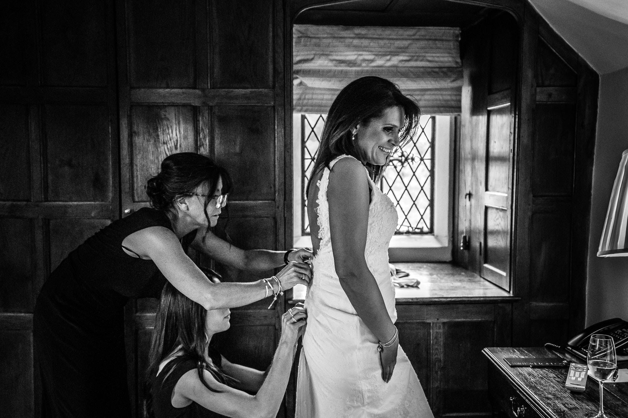 bridesmaids doing up wedding dress