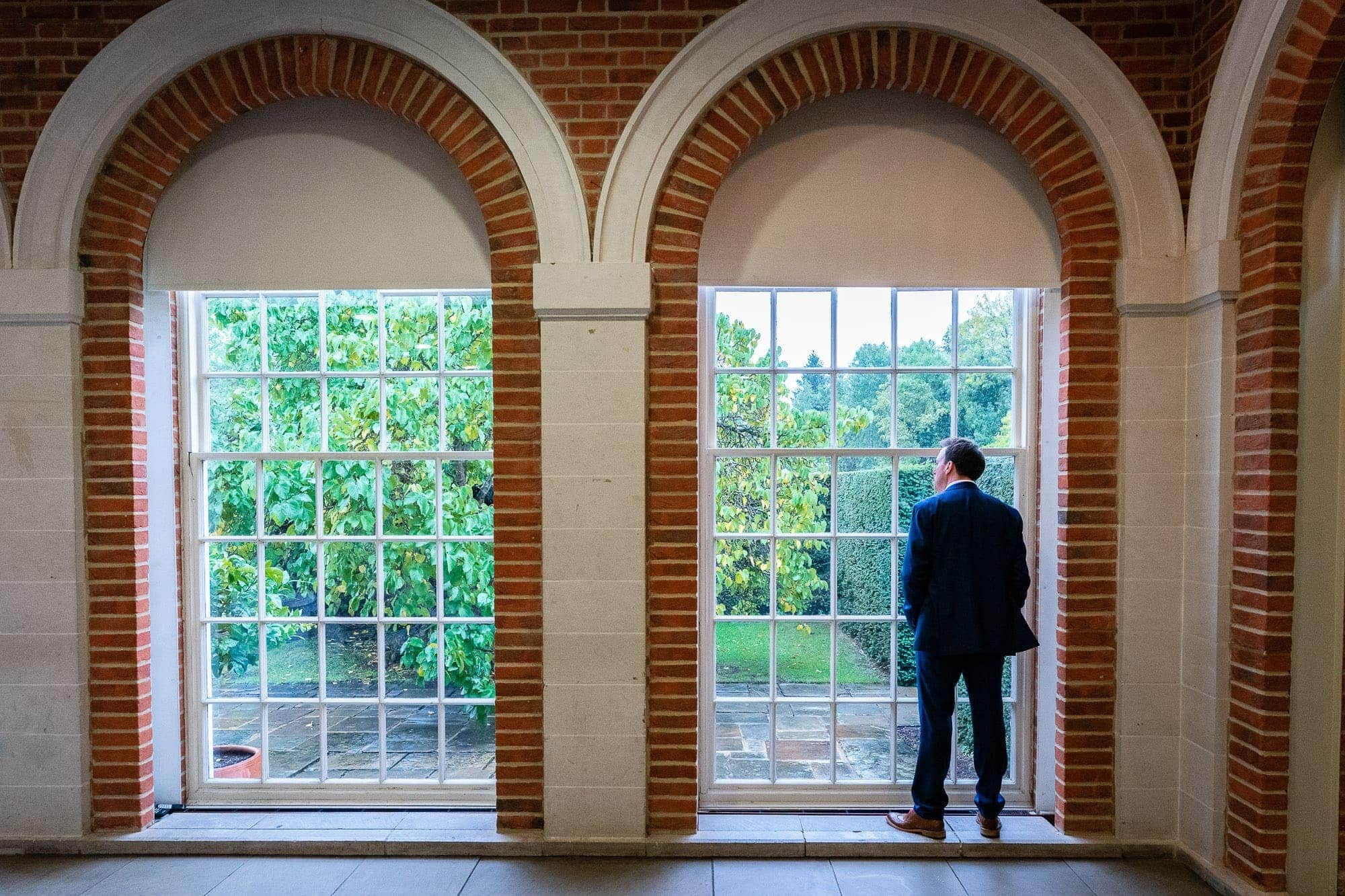 Groom looking at window in The Orangery at Great Fosters wedding
