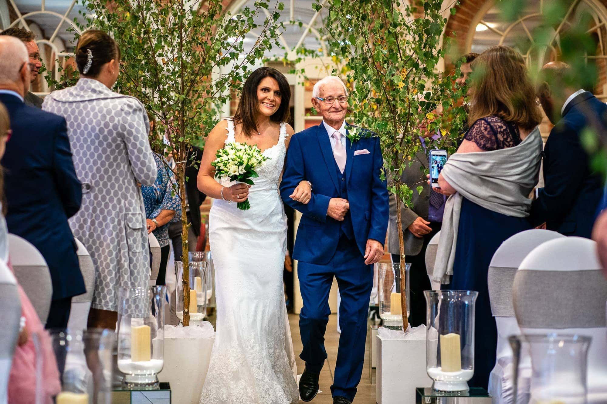 Bride and father walking down aisle in the Orangery at Great Fosters wedding